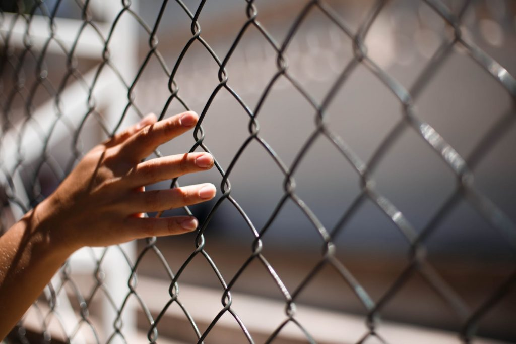 hand of crop person touching grid fence