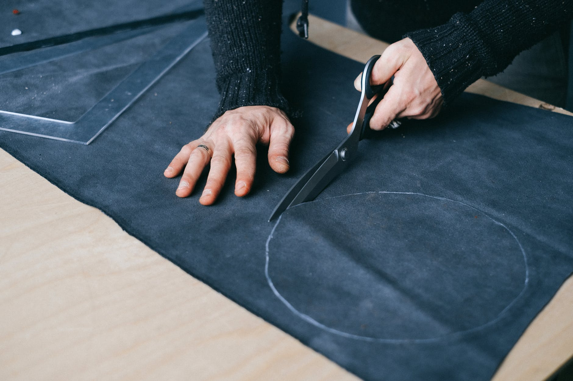 crop male artisan cutting piece of fabric at workbench