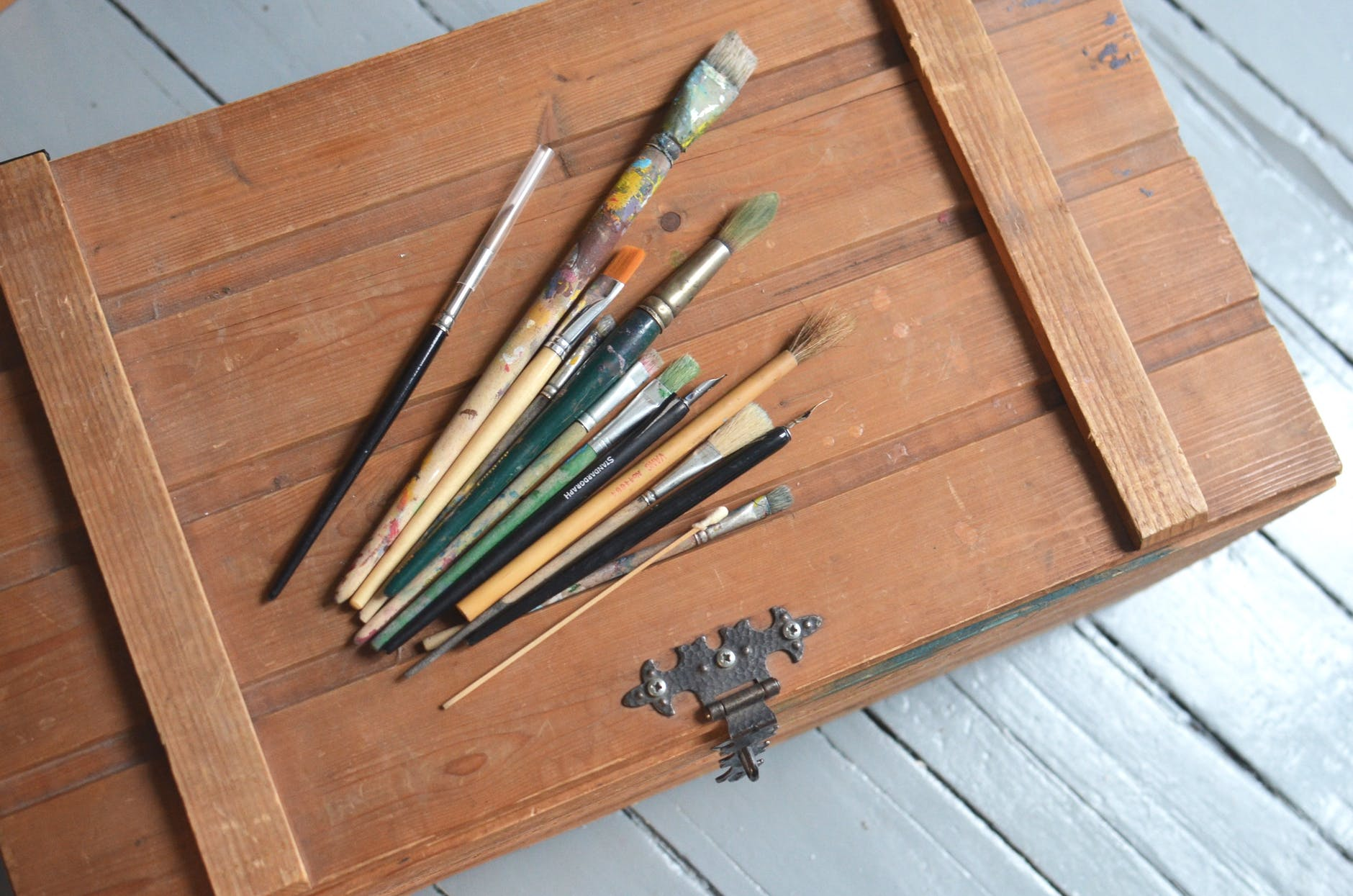 messy paintbrushes placed on wooden box