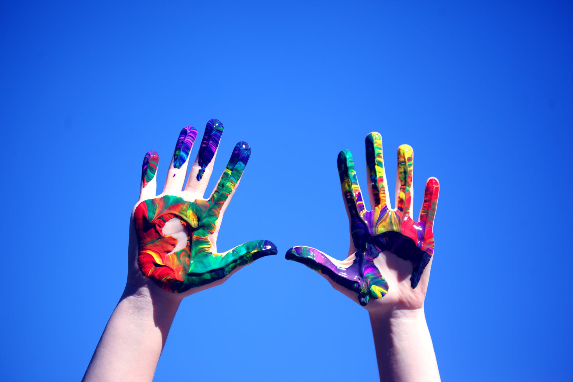 person s hands with paint