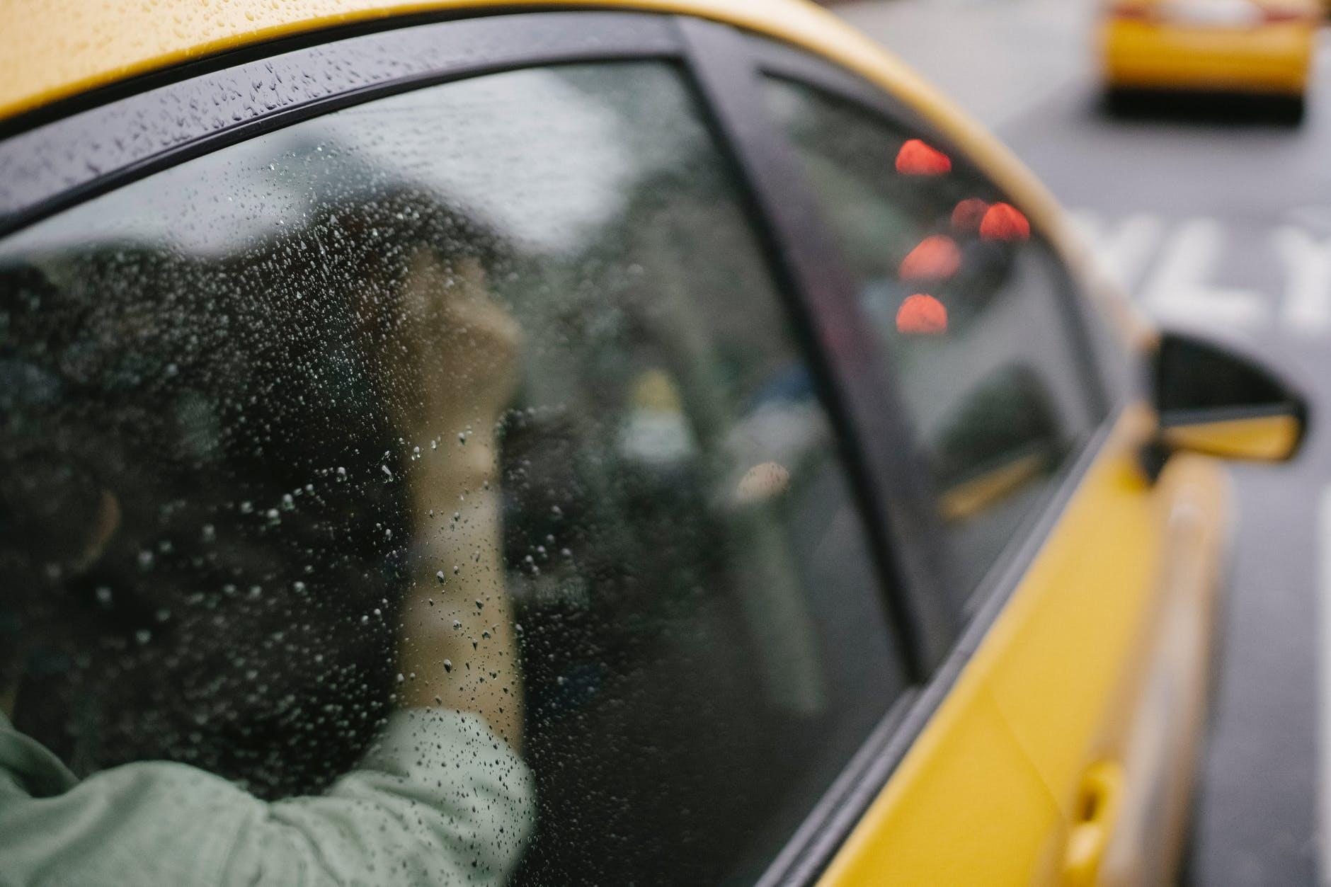 unrecognizable person in taxi automobile in city