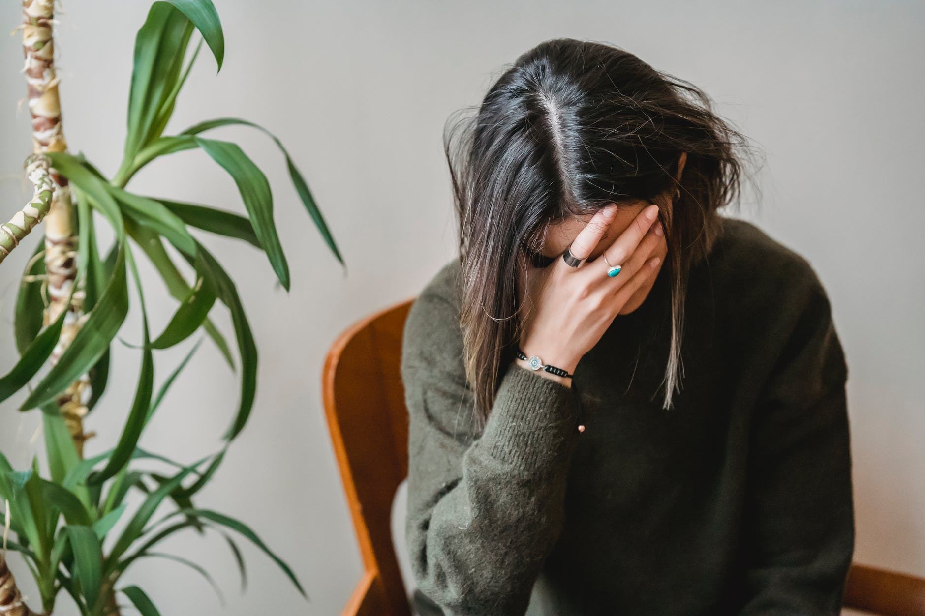 worried young woman covering face with hand