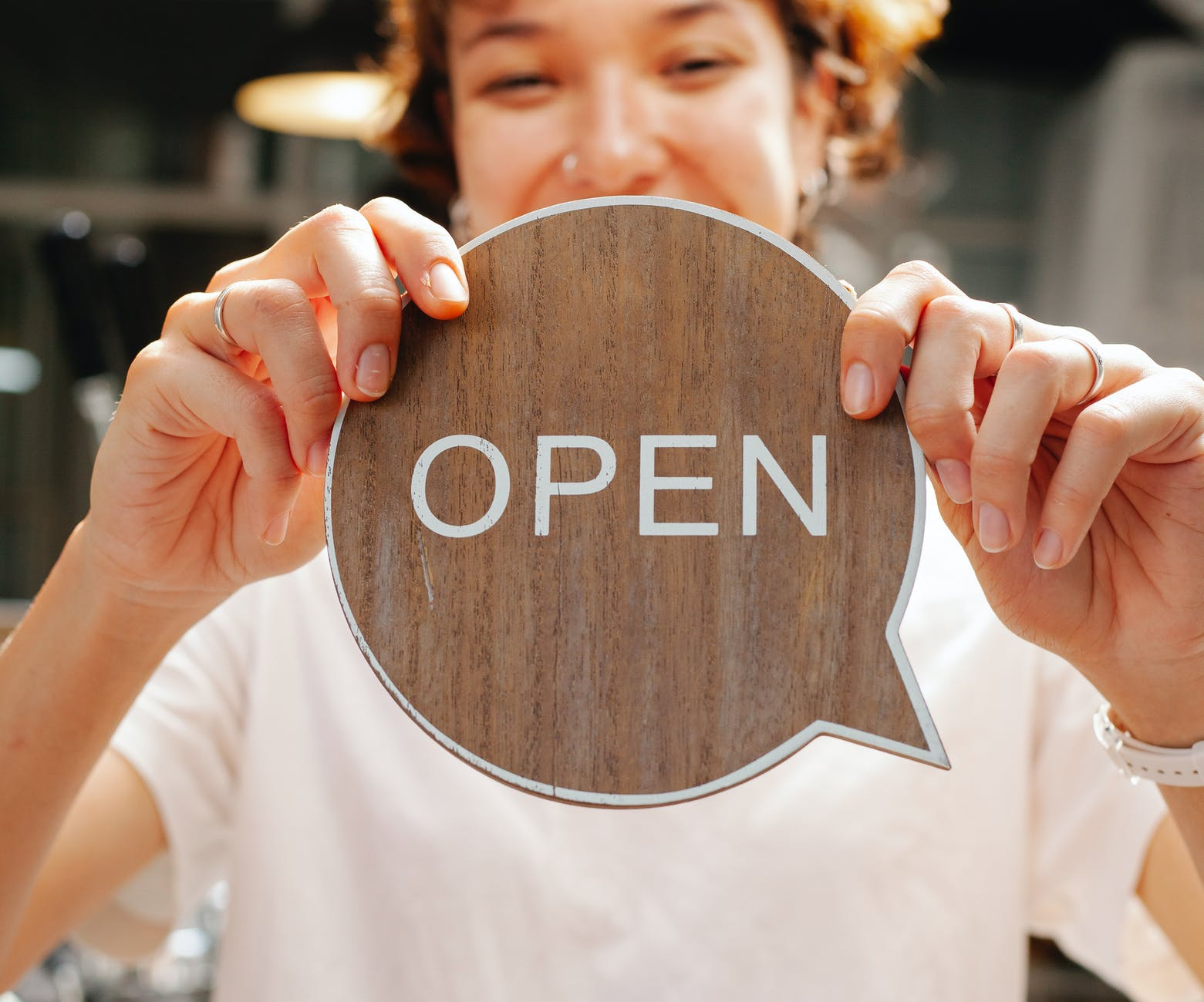 happy woman showing wooden signboard saying open